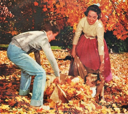 mid century family playing in fall leaves