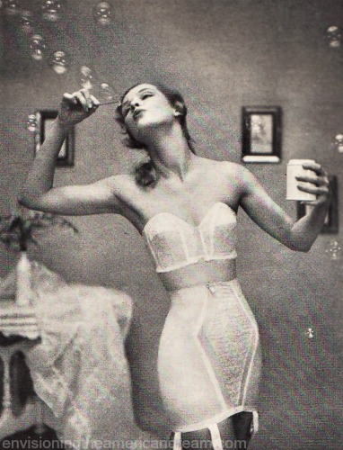 vintage photo 1950s woman in girdle and bra blowing bubbles