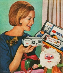 vintage 1960s mother holding camera at Xmas