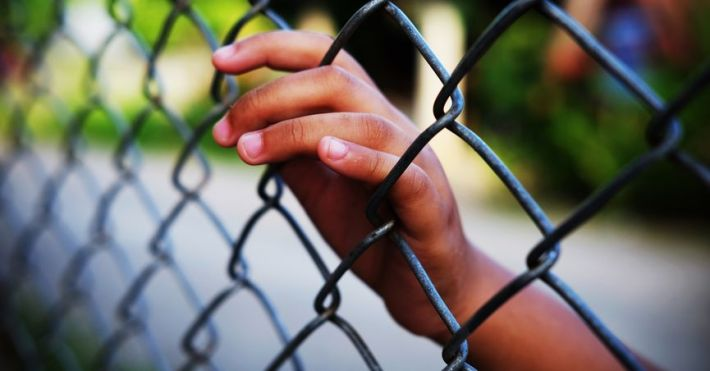 childs hand in fence
